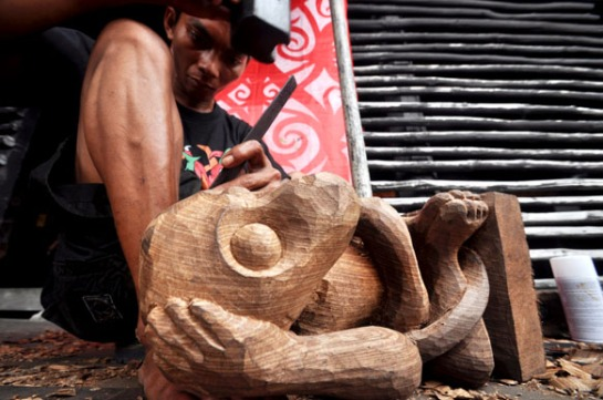 Seorang pria membuat pahatan patung khas dayak, saat mengikuti lomba